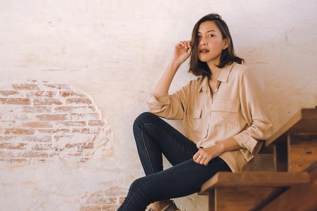 Una donna seduta a una vecchia scala in legno