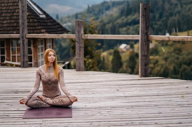 Una donna seduta nella posizione del loto al mattino su un'aria fresca.