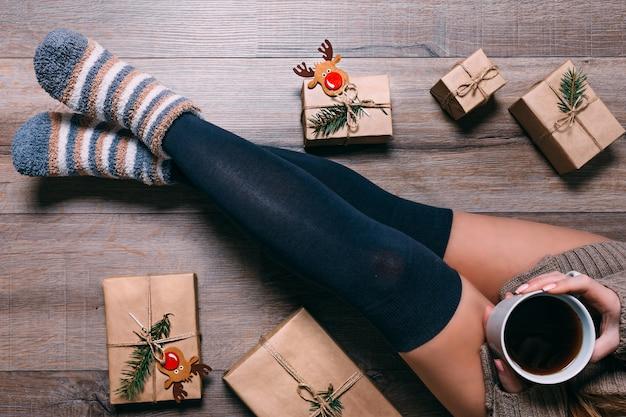 Una donna seduta sul pavimento che avvolge regali e beve il caffè nel periodo natalizio