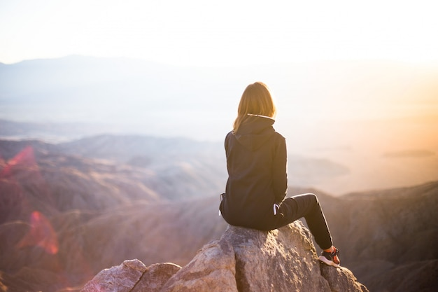 Una donna seduta sulla cima di una montagna