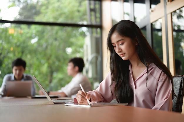 Una donna segretaria sta scrivendo su un tablet computer mentre era seduta nella sala riunioni.