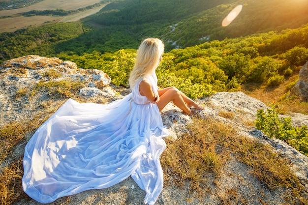 Una donna si siede su una roccia e guarda la splendida vista al sole
