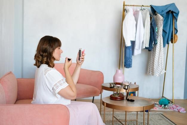 Una donna si siede sul divano nella stanza e dipinge le sue labbra