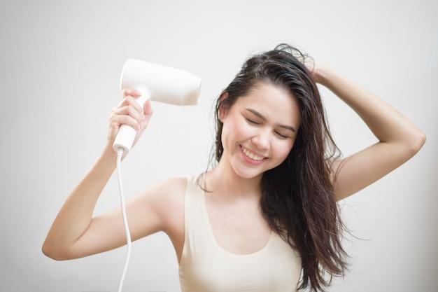 Una donna si sta asciugando i capelli dopo la doccia