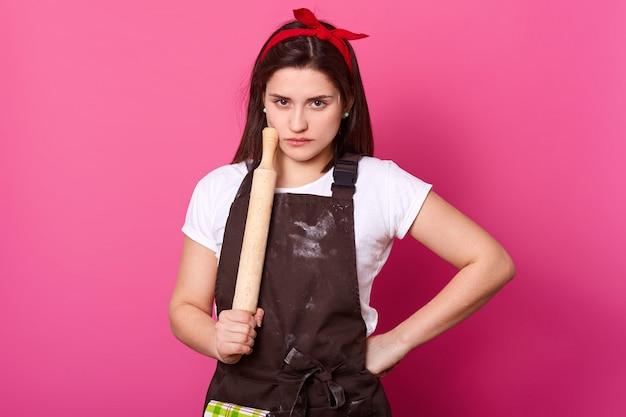 Una donna snella e seria tiene il mattarello, indossa un grembiule marrone imbrattato di farina, maglietta bianca e fascia rossa. la giovane ragazza carina ha uno sguardo duro stanco. cuoco isolato sulla parete rosa.