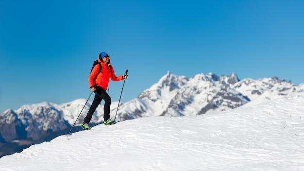 Una donna sola cammina sulla neve con i ramponi