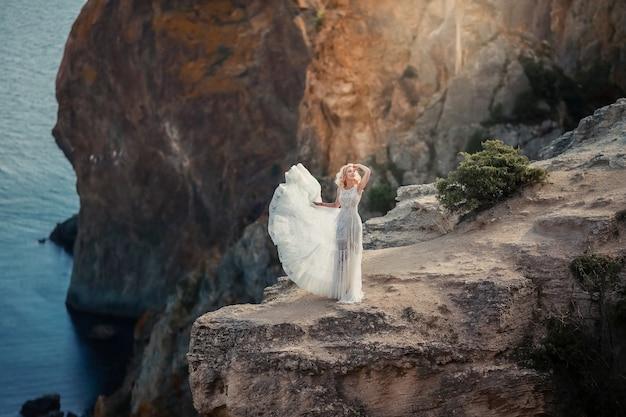 Una donna sola in un abito da sposa bianco sulla cima di una scogliera a picco sul mare