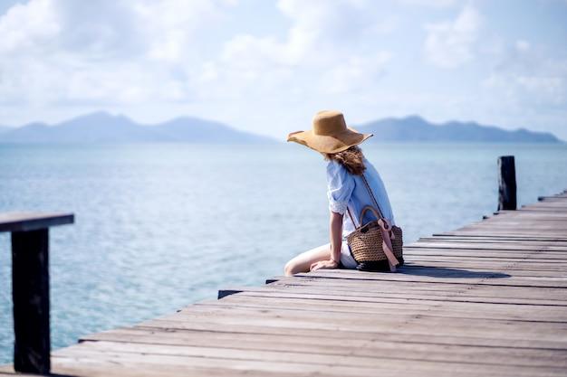 Una donna sola seduta sul ponte di legno - koh mark, thailandia