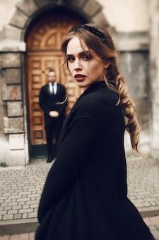 Una donna sorprendente in cappotto nero pone davanti a un vecchio edificio