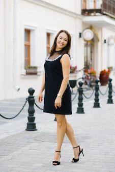Una donna sorridente di quarant'anni in un breve abito nero cammina attraverso la città estiva