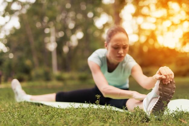 Una donna sta facendo stretching seduto su un tappeto per lo yoga.