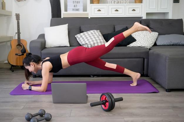 Una donna sta facendo yoga e guardando tutorial di formazione online sul suo laptop in salotto, allenamento fitness a casa, concetto di tecnologia sanitaria.
