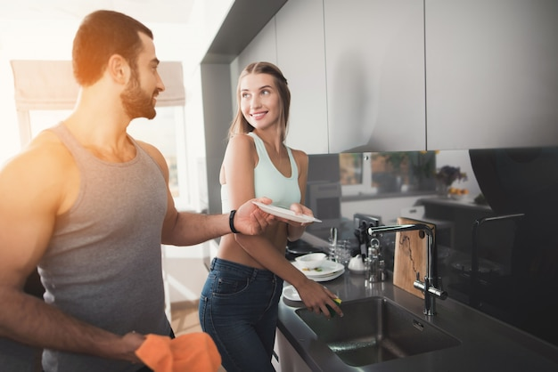 Una donna sta lavando i piatti, un uomo lo sta pulendo.