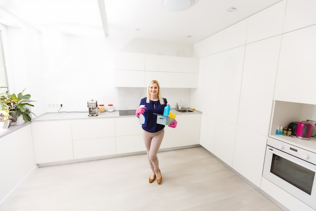 Una donna sta pulendo la cucina. lei sta guardando lontano dalla telecamera.
