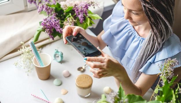Una donna sta scattando foto su una fotocamera del telefono cellulare di un caffè dalgona del mattino montato