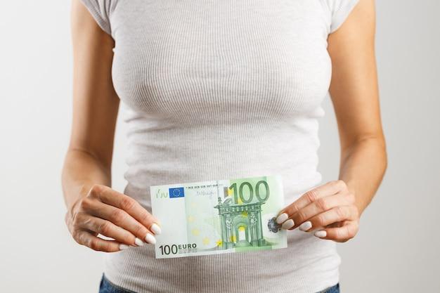 Una donna tiene in mano cento euro. concetto finanziario e commerciale.