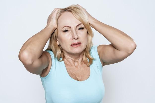Una donna tiene le mani sulla sua testa
