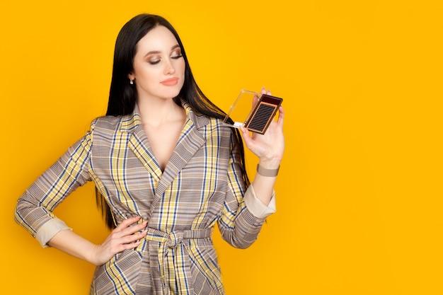 Una donna tiene un pacchetto di ciglia artificiali, un maestro dell'estensione delle ciglia su un muro giallo brillante, con spazio di copia. il concetto di estensione delle ciglia.