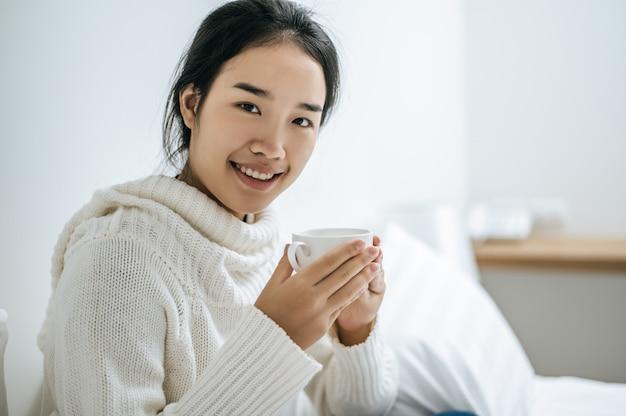 Una donna tiene una tazza di caffè.