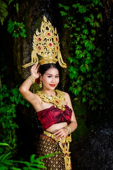 Una donna vestita con un abito thailandese antico presso la cascata.