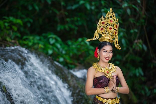 Una donna vestita con un antico abito thailandese alla cascata.