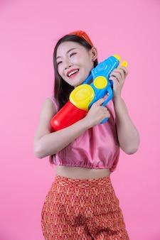 Una donna vestita in abiti tradizionali tailandesi tradizionali tenendo una pistola ad acqua su uno sfondo rosa.