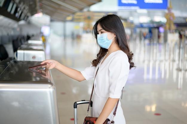 Una donna viaggiatrice indossa una maschera protettiva in aeroporto internazionale, viaggia sotto la pandemia covid-19,
