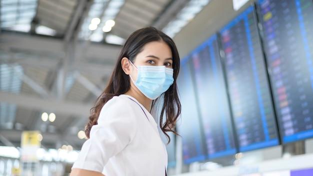 Una donna viaggiatrice indossa una maschera protettiva in aeroporto internazionale, viaggia sotto pandemia covid-19, viaggi di sicurezza, protocollo di allontanamento sociale, nuovo concetto di viaggio normale.