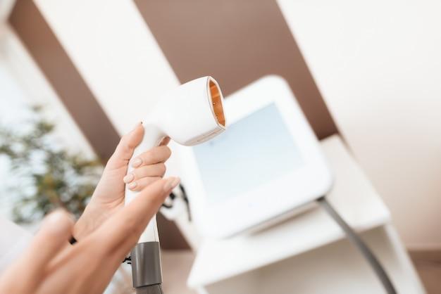 Una dottoressa detiene un dispositivo per la depilazione laser