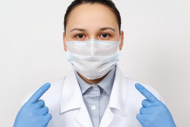 Una dottoressa in vestaglia e guanti indica con le mani una maschera respiratoria protettiva