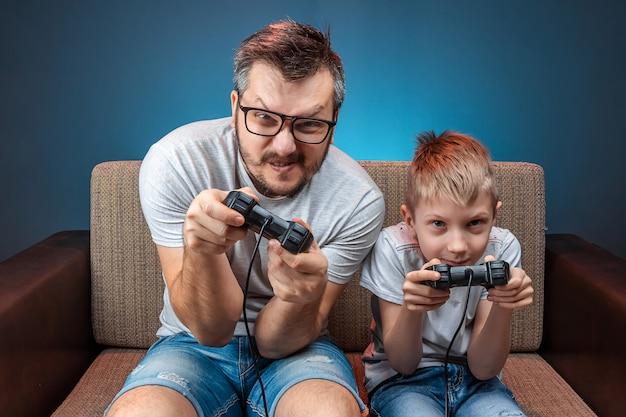 Una famiglia allegra, papà e figlio giocano sulla console, nei videogiochi, reagiscono emotivamente mentre sono seduti sul divano. giorno libero, divertimento, svago, trascorrere del tempo insieme.