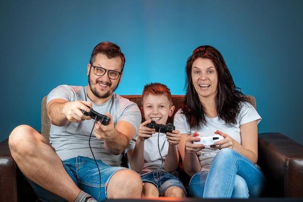 Una famiglia allegra, papà mamma e figlio giocano sulla console, i videogiochi, reagiscono emotivamente seduti sul divano. giorno libero, divertimento, svago, trascorrere del tempo insieme.