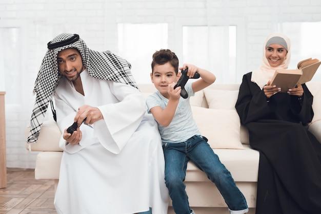 Una famiglia araba tradizionale gioca su una console di gioco.