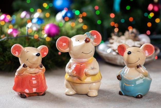 Una famiglia di figurine in ceramica di topi su luci di natale.