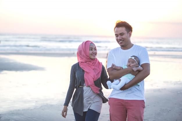 Una famiglia di tre felice che gode dell'estate alla spiaggia