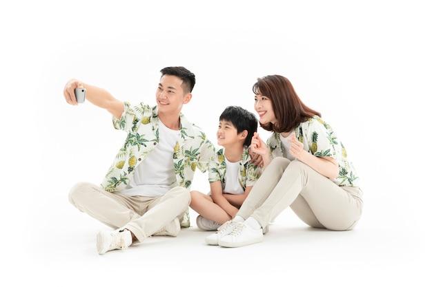 Una famiglia di tre felice che si siedono sulla terra e che prendono selfie