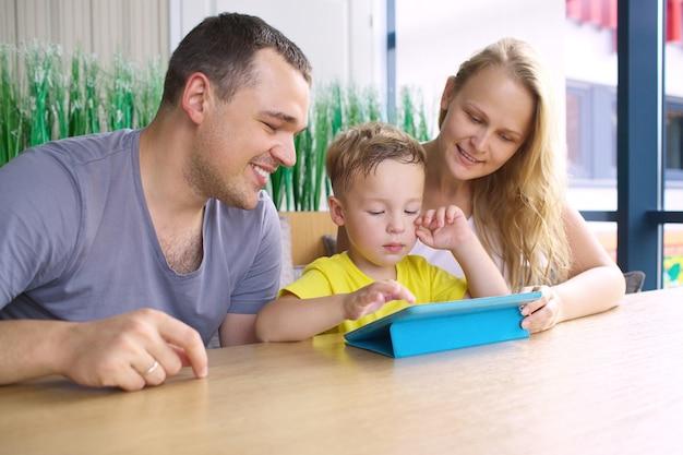 Una famiglia di tre felice con il computer della compressa in caffè