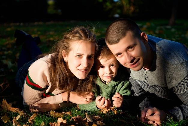 Una famiglia di tre persone gode del parco in autunno divertendosi con il sorriso