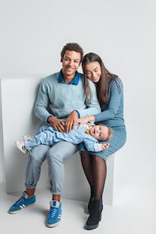 Una famiglia felice dell'uomo afro e donna e bambino caucasici sullo studio bianco