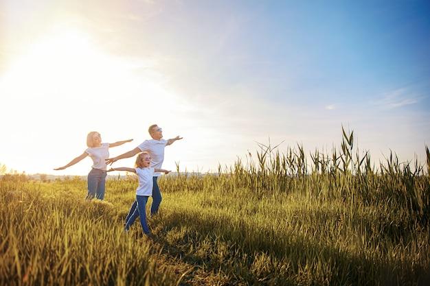 Una famiglia felice in magliette bianche, occhiali da sole e jeans nel parco