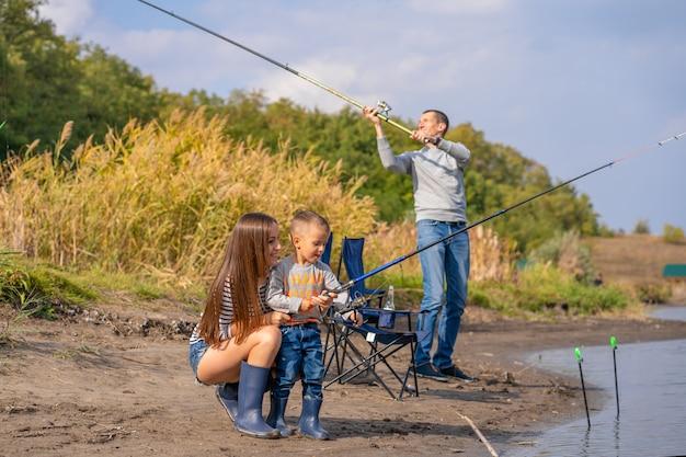 Una famiglia felice trascorre del tempo insieme, insegnano al figlio a pescare.
