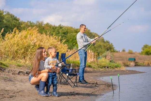 Una famiglia felice trascorre del tempo insieme; insegnano al figlio a pescare.
