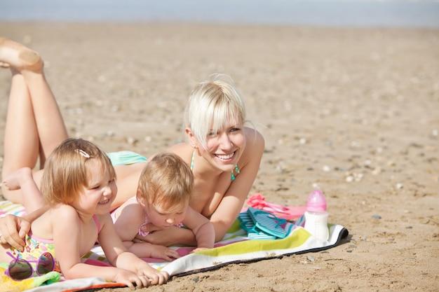 Una famiglia ridendo sdraiata in spiaggia