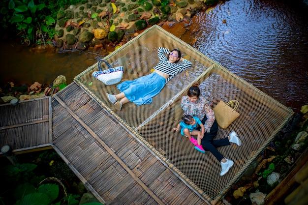 Una felicità di due bambini della ragazza e della donna sul terrazzo di bambù naturale