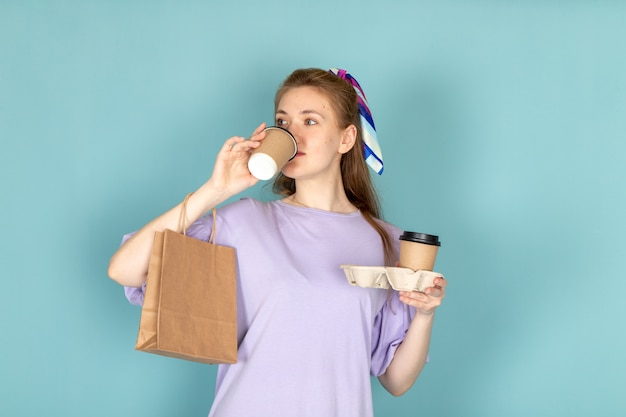 Una femmina attraente di vista frontale in camicia-vestito blu che tiene pacchetto di carta e tazze di caffè che bevono sull'azzurro