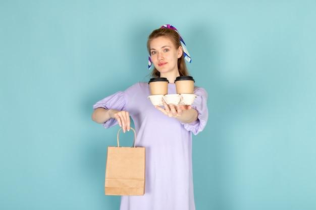 Una femmina attraente di vista frontale in camicia-vestito blu che tiene pacchetto di carta e tazze di caffè sull'azzurro