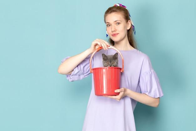 Una femmina attraente di vista frontale in camicia viola che tiene secchio rosso con il gattino sveglio sull'azzurro
