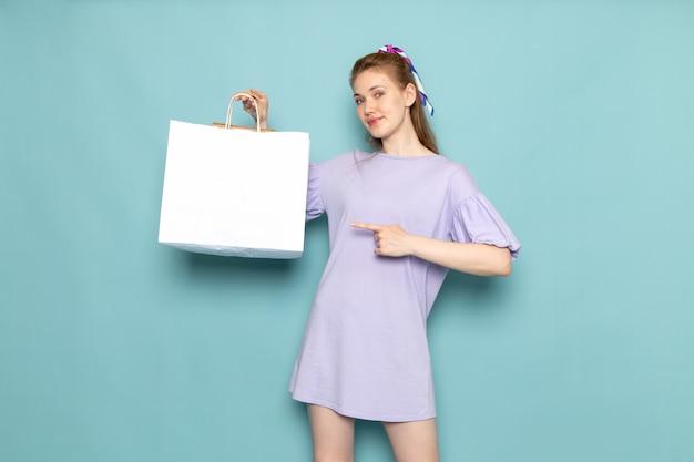 Una femmina attraente di vista frontale in vestito blu che tiene il pacchetto di acquisto sull'azzurro