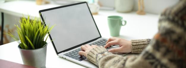 Una femmina che lavora al computer portatile dello schermo in bianco con la tazza da caffè e la decorazione sul worktable semplice