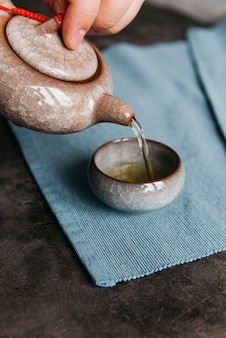 Una femmina che versa il tè dalla teiera di ceramica nella tazza da tè